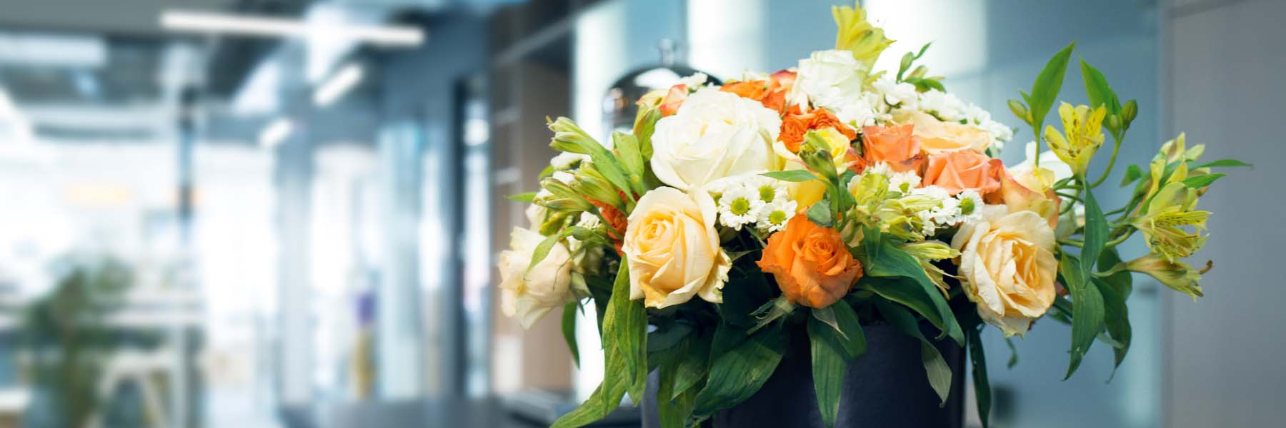 Bright bouquet of freshly cut flowers including orange roses and mixed foliage in an office environment