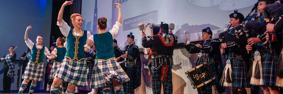 A stage of Scottish Highland dancers in traditional dress dancing to a live Pipe band