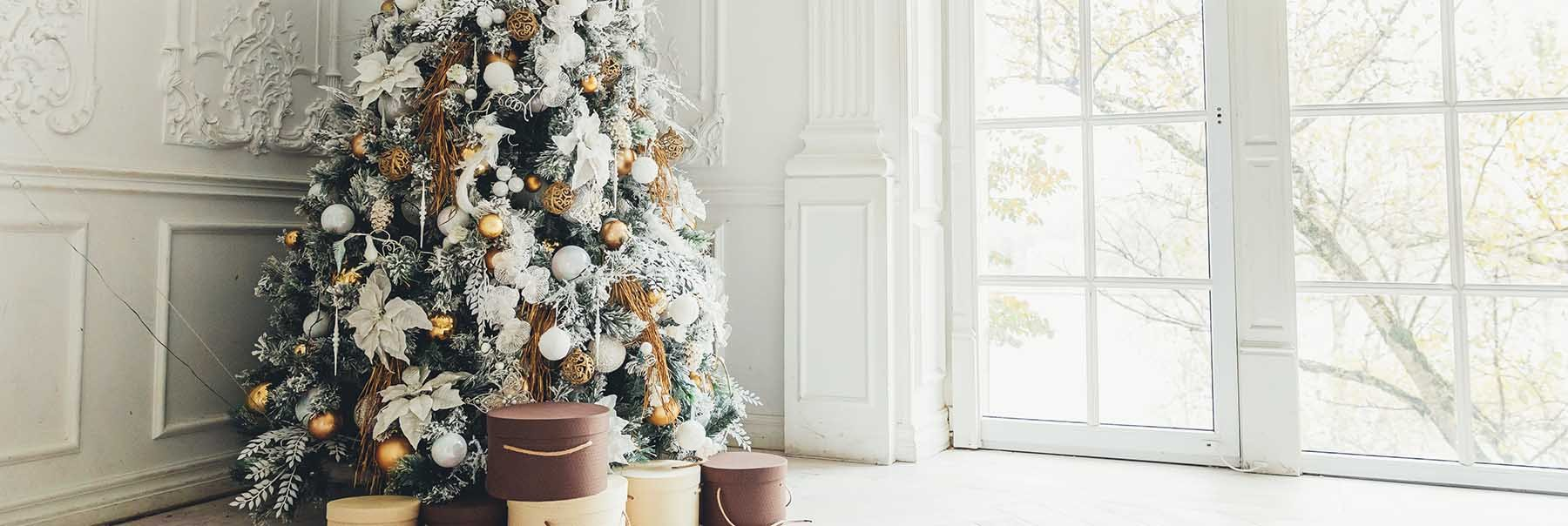Beautifully decorated Christmas tree in front of a traditional glass door in a luxe bright wood panelled living room