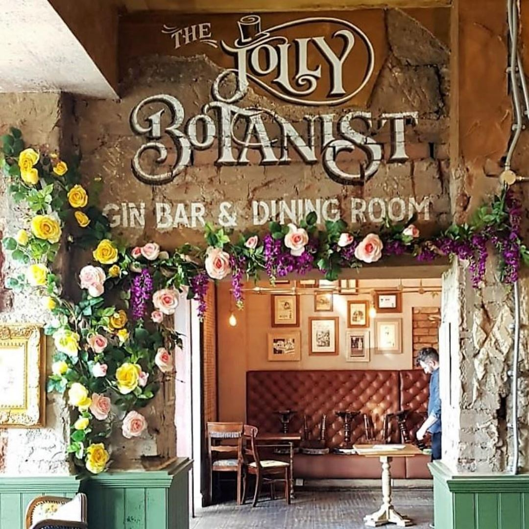 Jolly Botanist Gin Bar in Falkirk welcomes guests with a bespoke climbing vine of artificial roses, wisteria and foliage