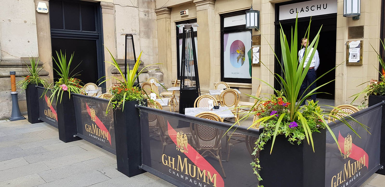 French style bistro pavement café outdoor dining at Glaschu in Glasgow with lush planters and bespoke branded banners