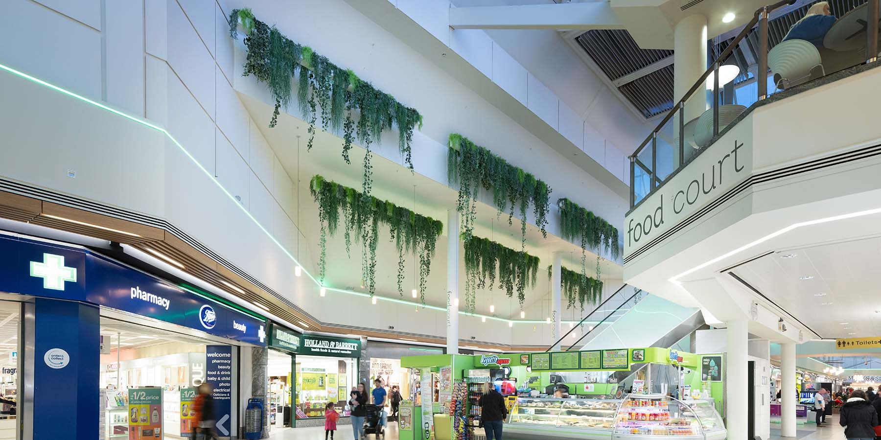 Trailing mixed artificial foliage cascades from bespoke hanging troughs high above retail units at Gyle Centre Edinburgh