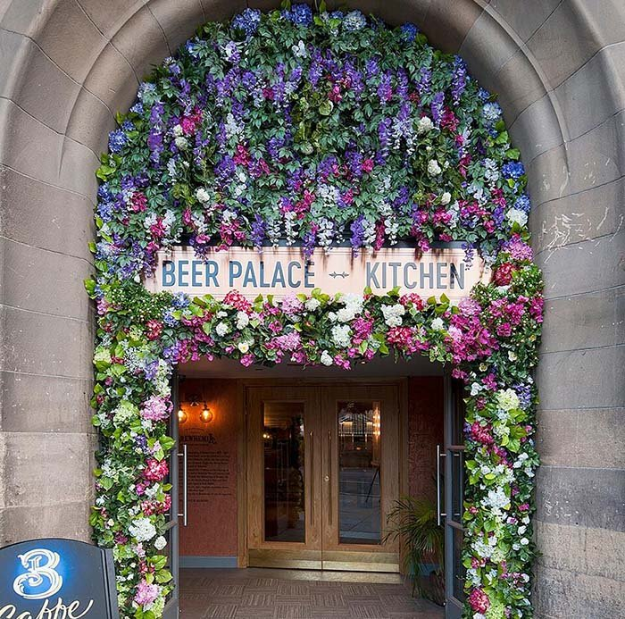 Floral archway bursting with colourful artificial flowers and lush greenery welcomes guests at Brewhemia Edinburgh