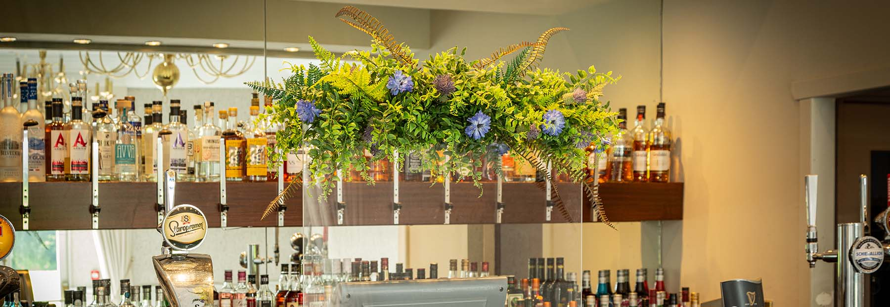 Hotel Bar with a PPE screen in front of the till topped with floral display of artificial foliage, flowers, and thistles