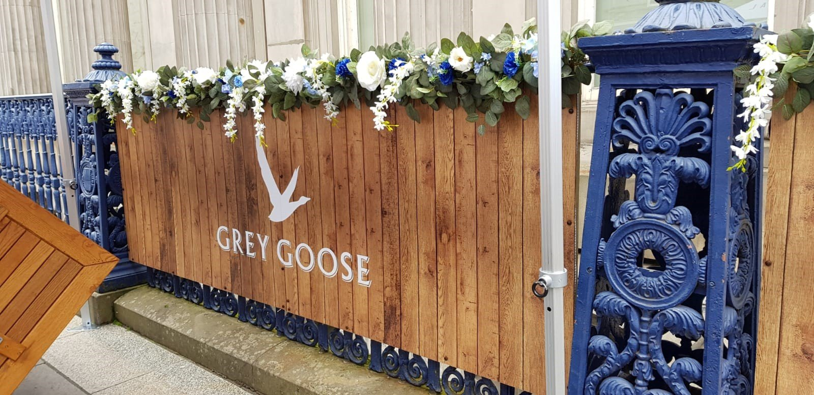 Grey Goose vodka branded panels to zone outdoor dining space decorated with artificial plants and blue and white florals