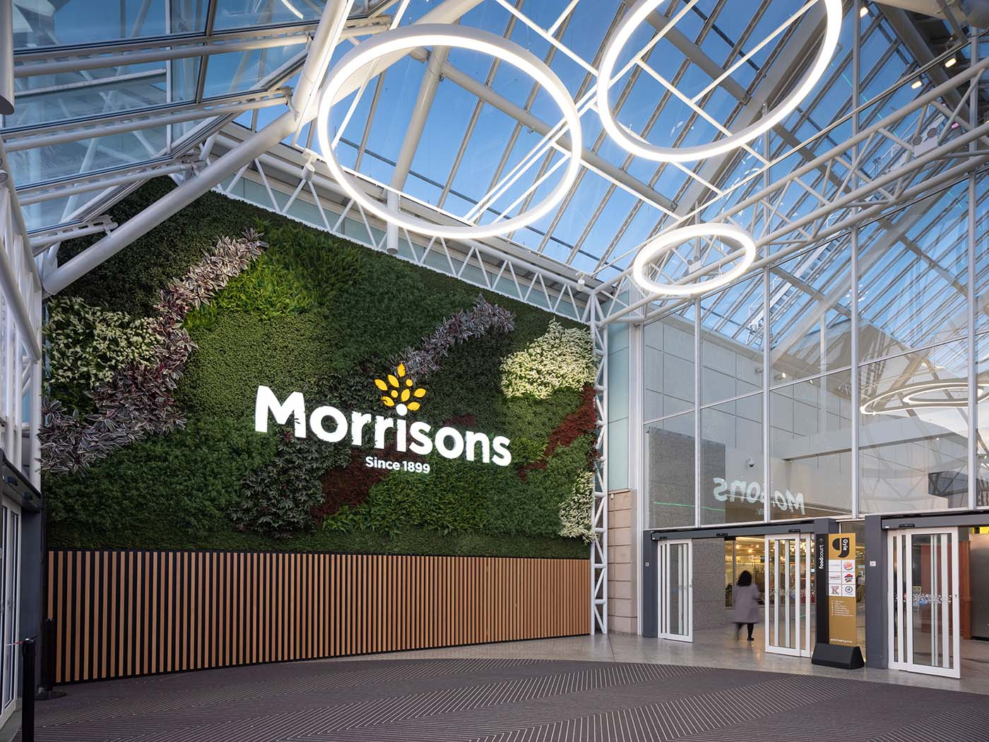 Huge green wall with Morrisons branding at Gyle Shopping Centre Edinburgh planted with artificial plants and Nordik Moss