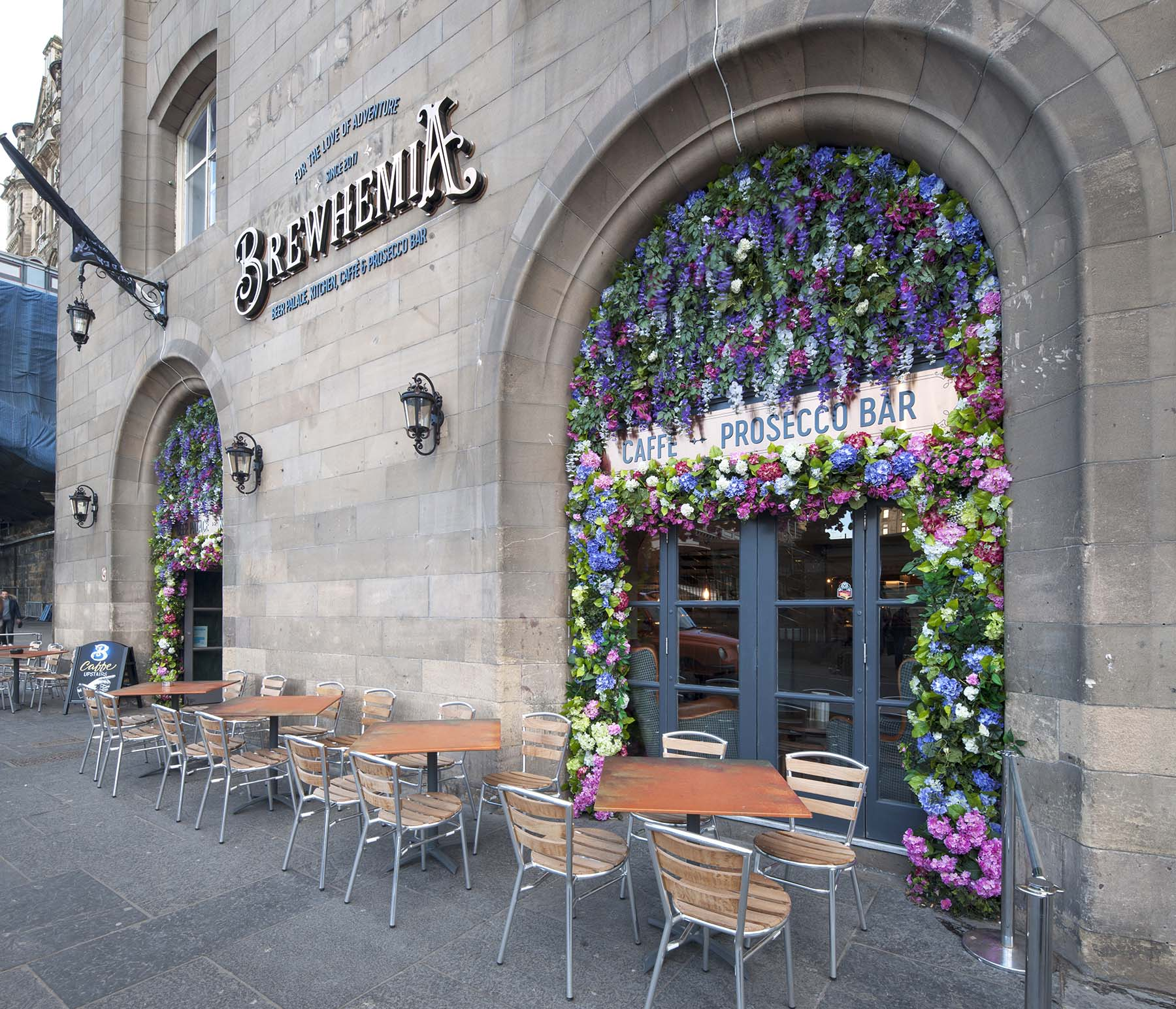Huge floral frontage feature at Brewhemia Edinburgh with bright colourful artificial flowers for eye-catching entrance