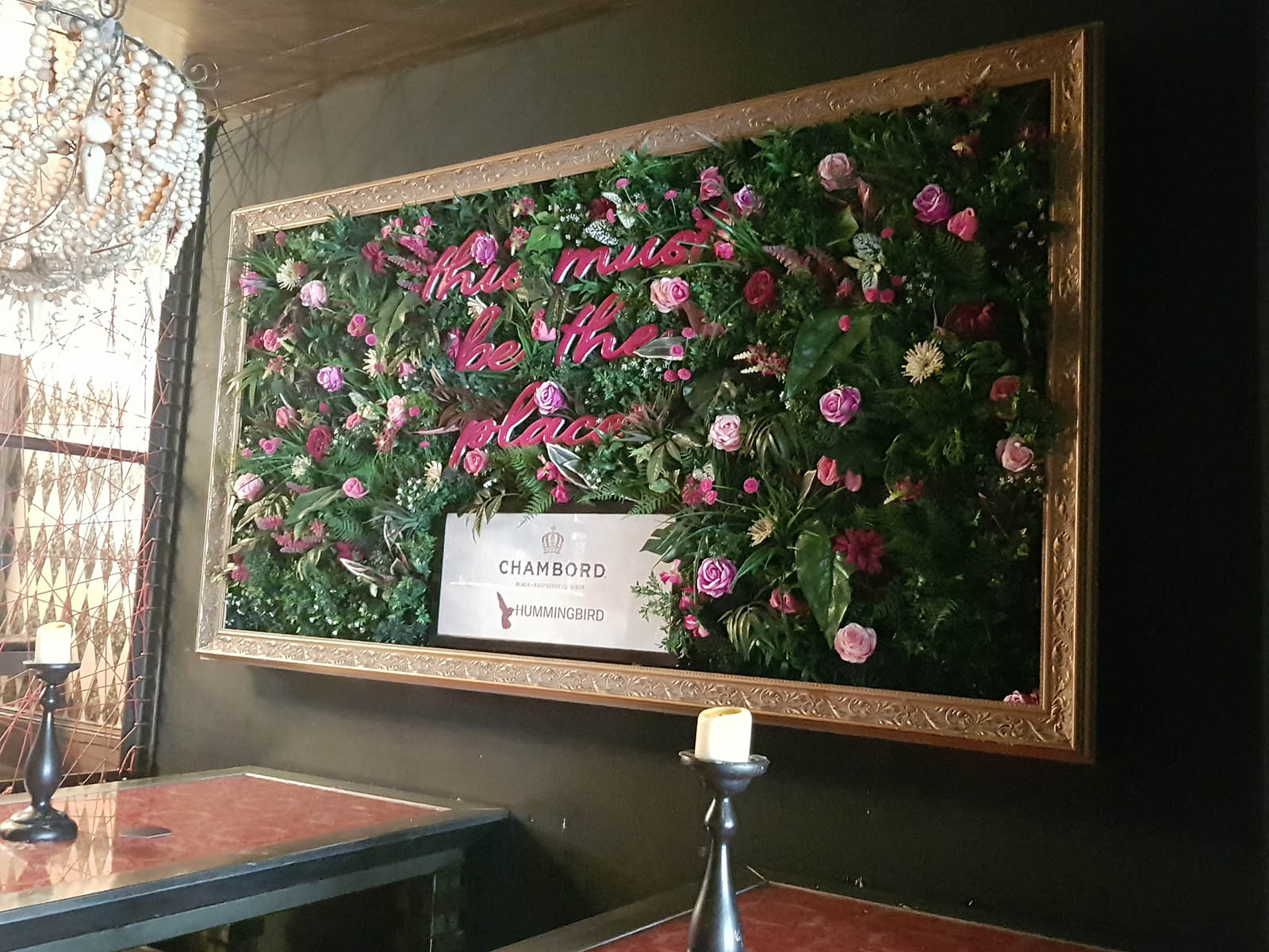 Chambord branded bespoke artificial foliage wall with pink flowers, neon signage and gold frame in Glasgow cocktail bar