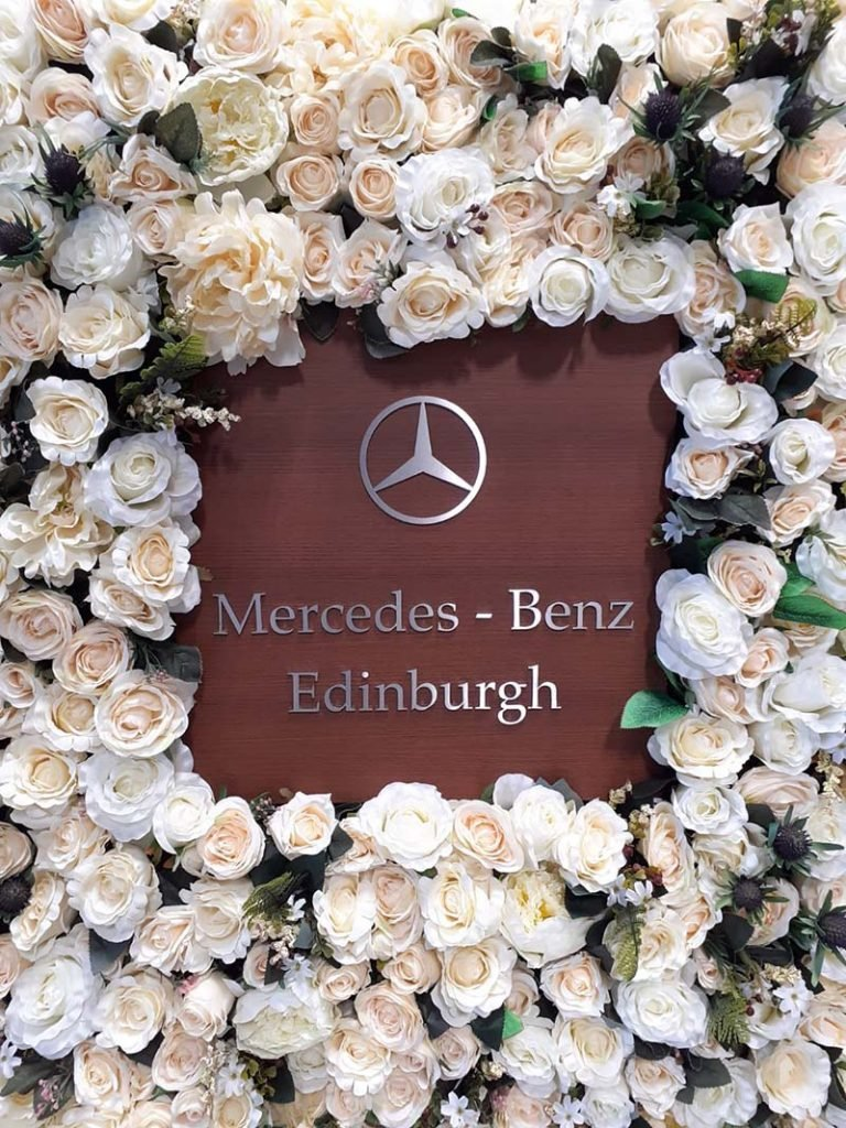 Bespoke branded artificial rose and thistle floral wall for Mercedes Benz Edinburgh car showroom handover area
