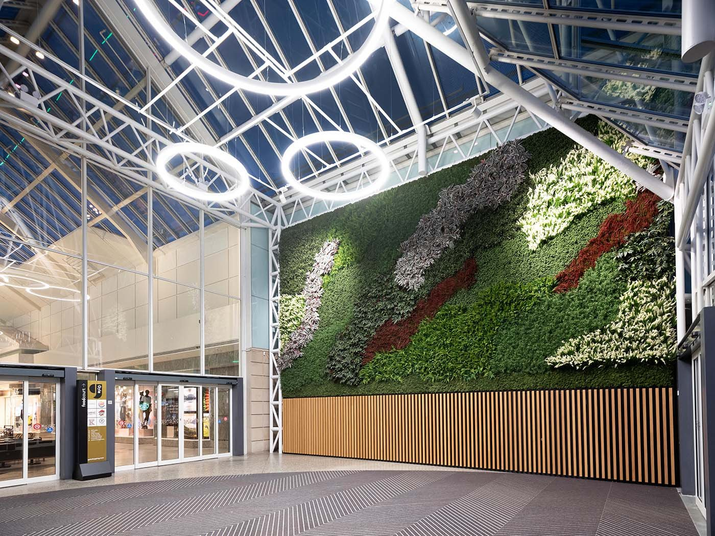 Beautiful green wall with swathes of varied artificial plants and Nordik Moss welcomes shoppers at Gyle Centre Edinburgh