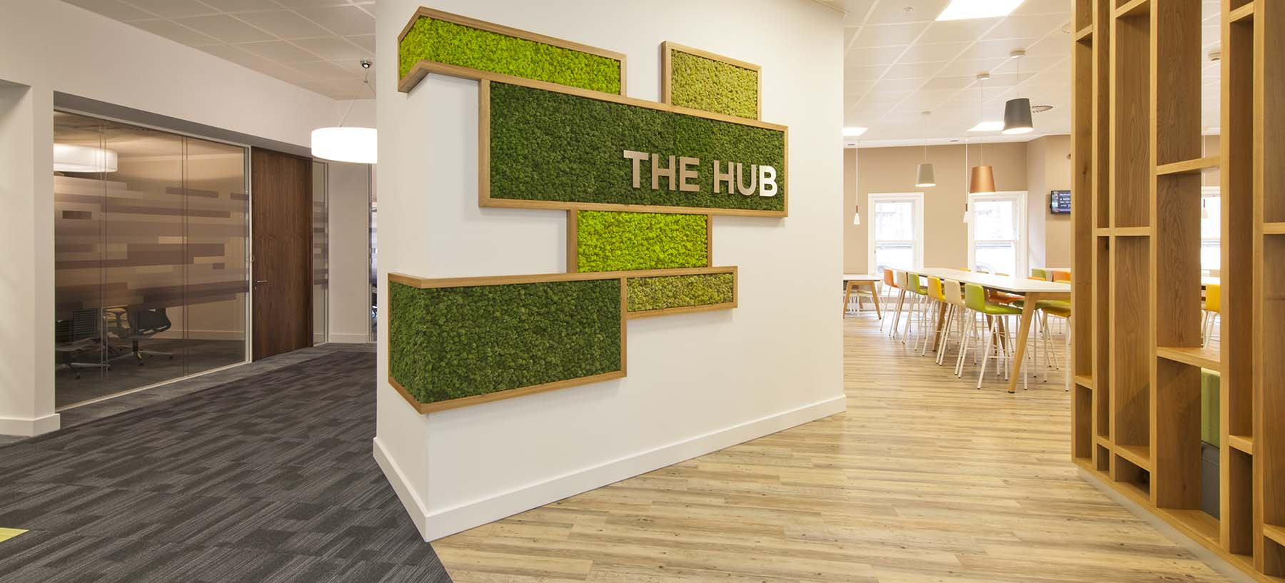 Wraparound Nordik Moss wall feature in bespoke oak frame with stainless steel signage for Glasgow office breakout area