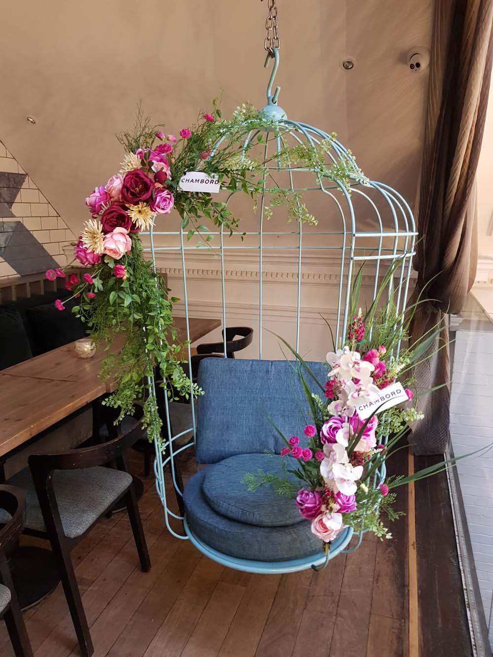 A hanging birdcage seat in Hummingbird Glasgow adorned with artificial floral displays and Chambord branding