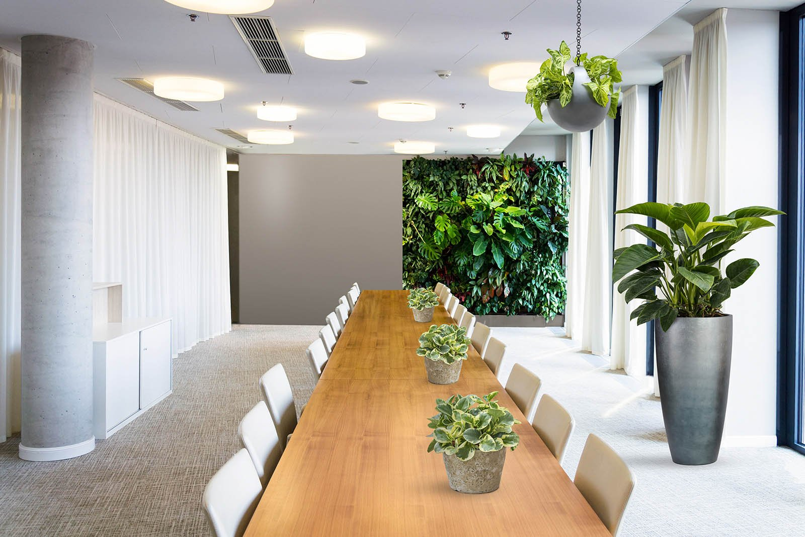 Mock-up of an office space with one half filled with a green wall, lush plants and hanging greenery, the other half bare