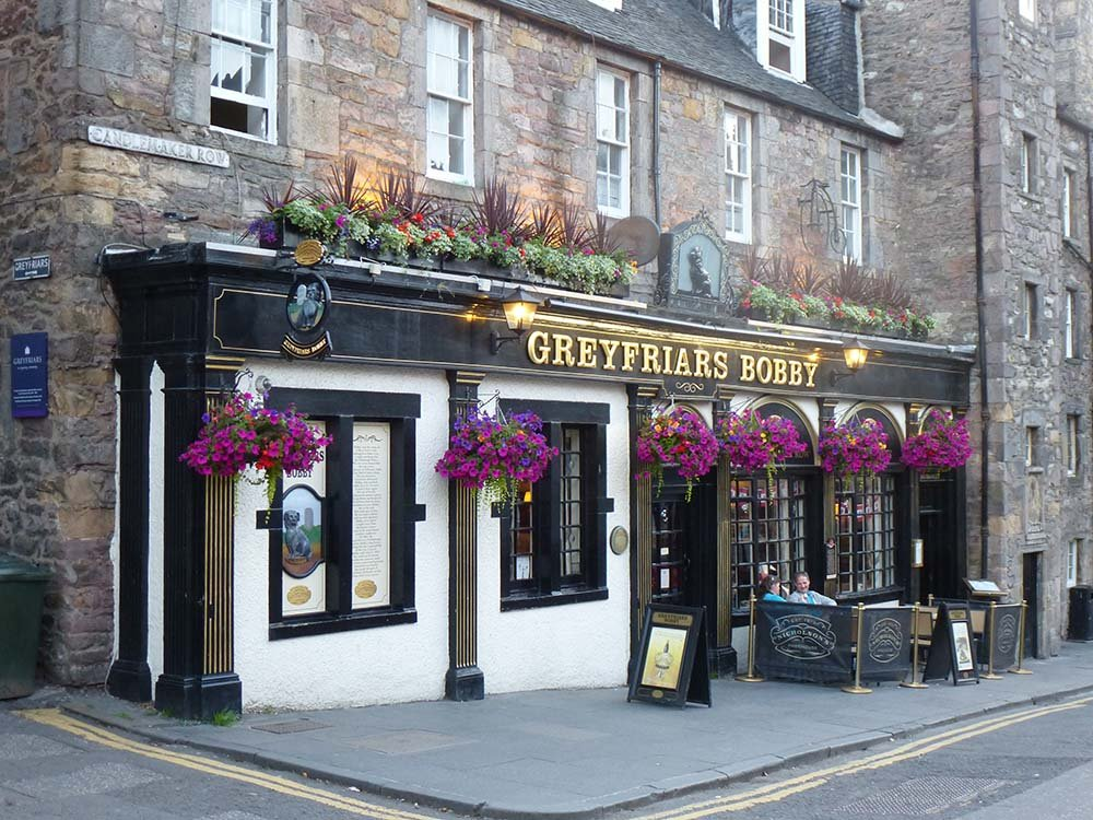 Blooming hanging baskets bursting with colourful plants and flowers at the Greyfriars Bobby Bar in Edinburgh's Old Town