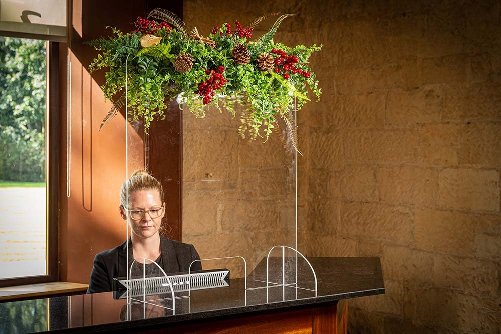 Hotel reception screen decorated with seasonal floral screen topper inc greenery, red berries and natural pine cones