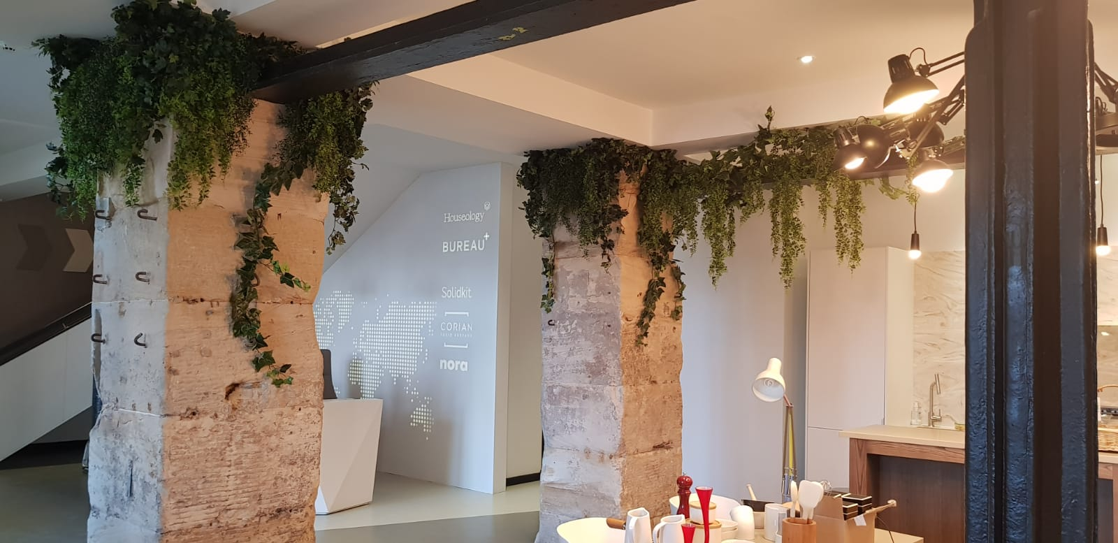 Traditional stone columns and exposed beams in converted offices draped with ivy and foliage make it warm and welcoming