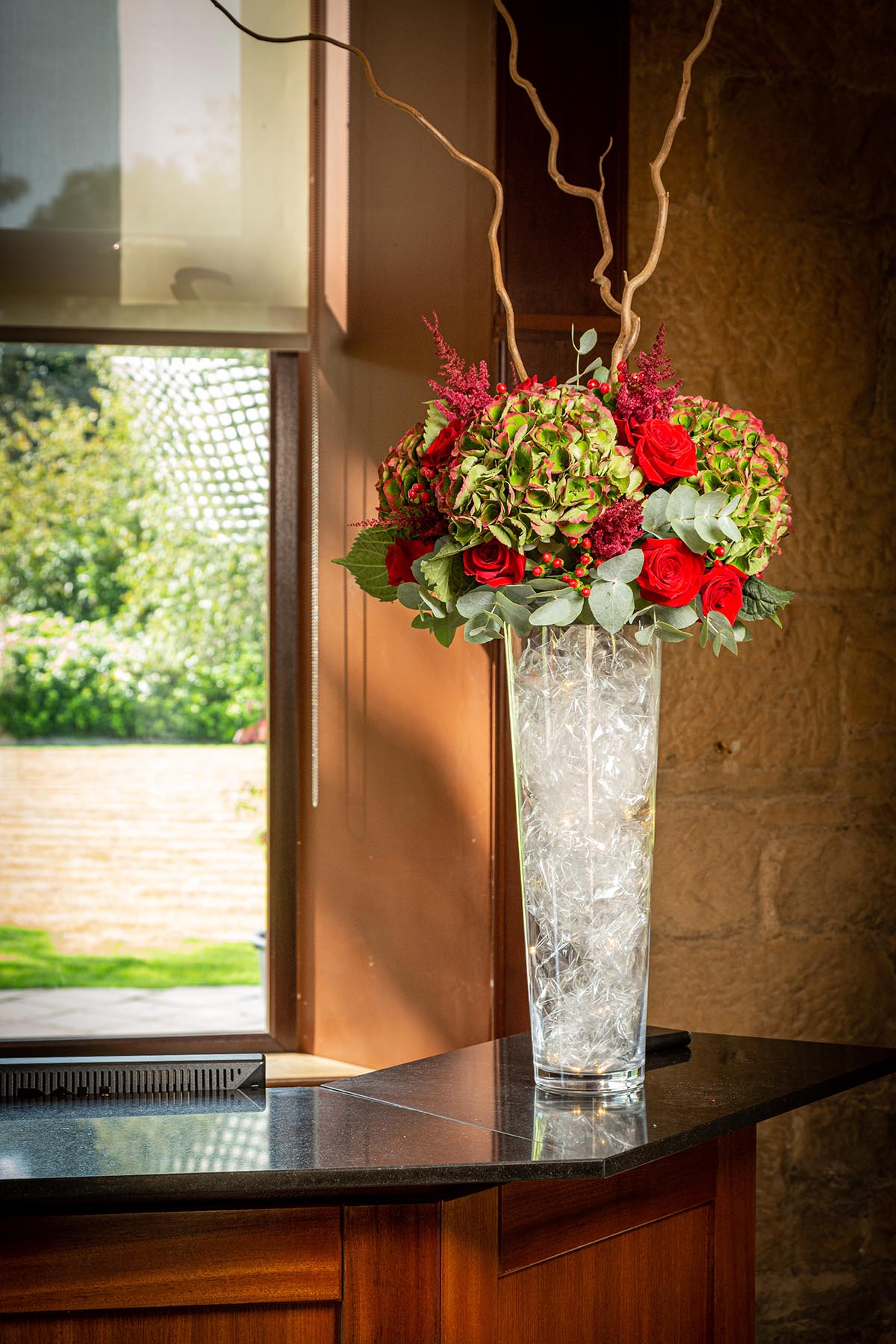 A tall glass vase with hydrangea, red roses and willow on the reception desk at Glenbervie House Hotel, Larbert