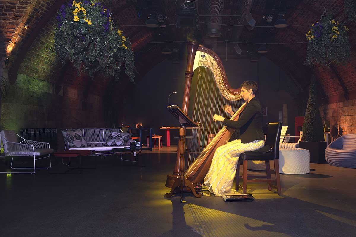 A Harpist plays at Bureau Night Garden event in Glasgow's Arches. Venue dressed with exterior planters and hanging foliage