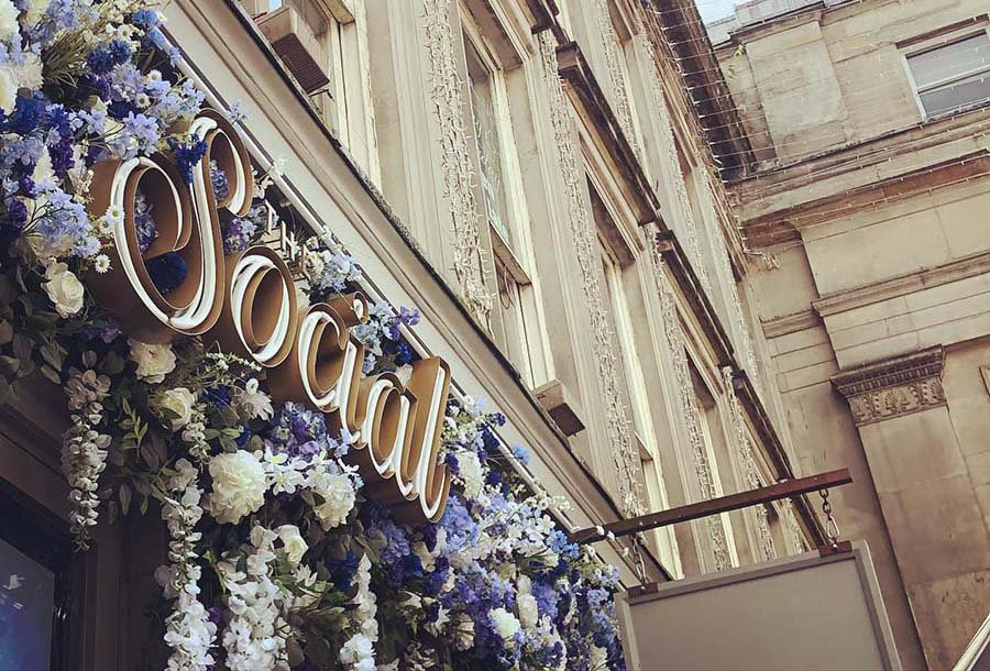 The Social in Glasgow with bespoke signage and a floral frontage of purple and white hydrangea and wisteria flowers