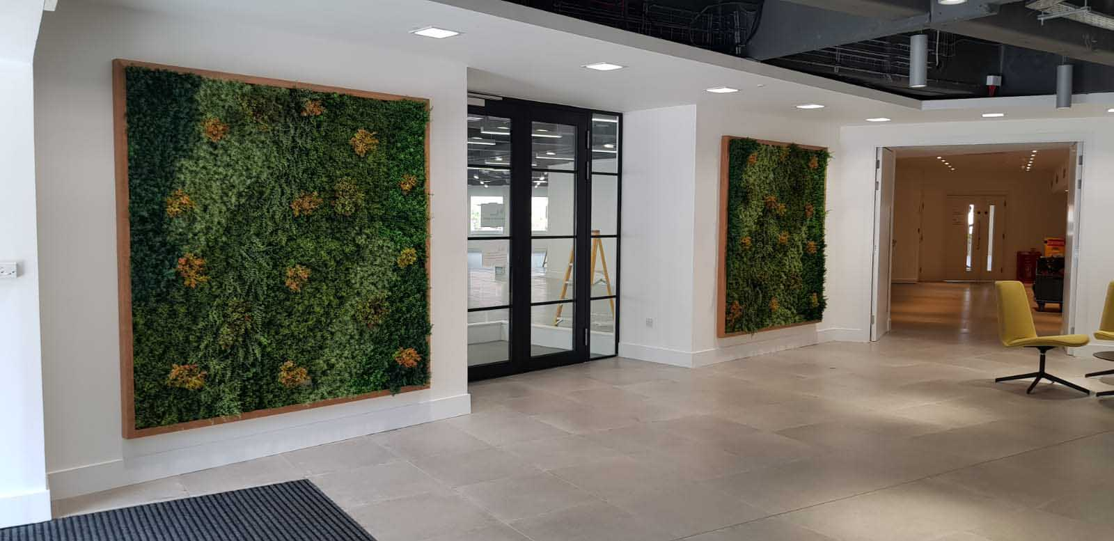 Bespoke artificial green wall foliage panels full of tones and texture in wooden frames hung in office entrance area