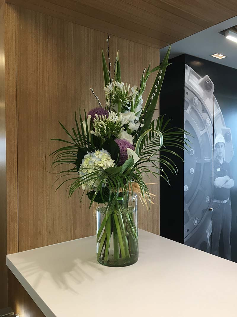 A commercial fresh flower arrangement in glass vase on reception desk provides a warm welcome to visitors