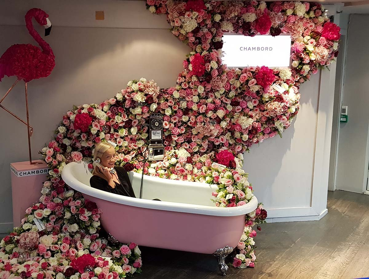 October's Ultimate Chambord selfie spot! Woman in vintage bath overflowing with pink and white roses, fun phone, flamingo