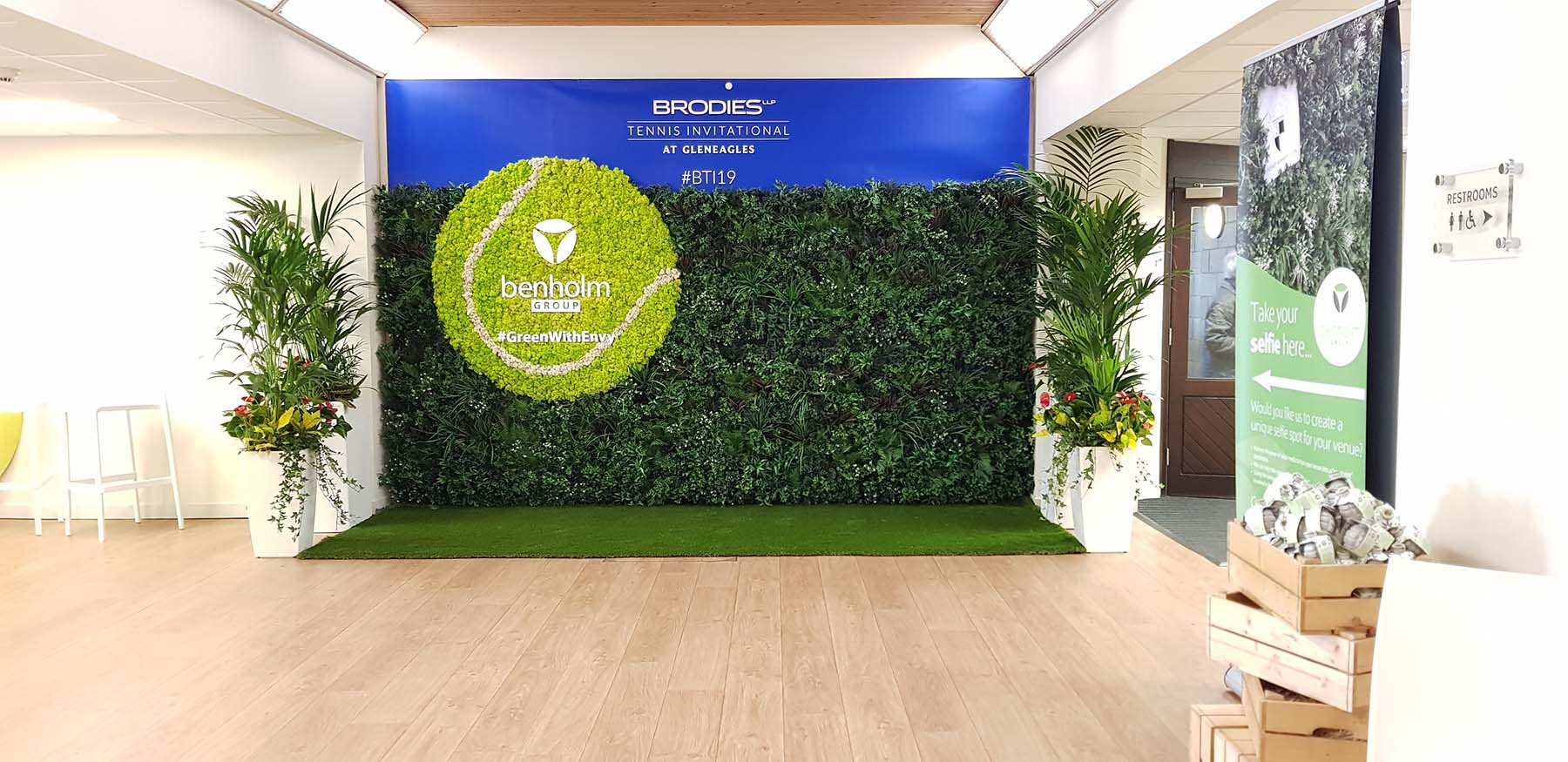 Bespoke selfie wall for Brodies' event at Gleneagles Hotel with green wall, Nordik Moss tennis ball and live Kentia palms
