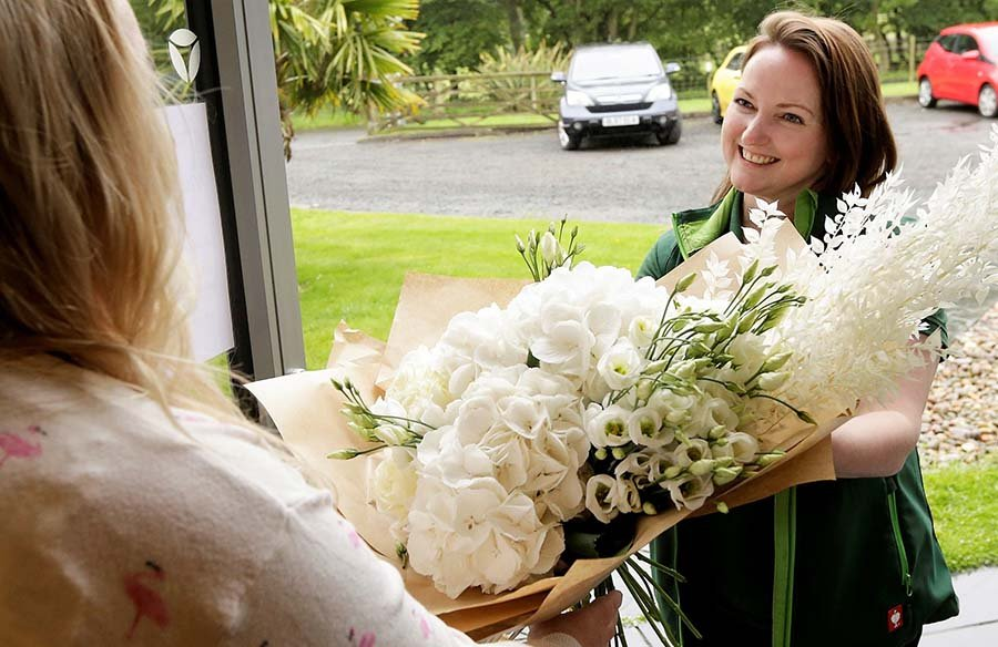Beautiful large bouquet of hydrangea and lisianthus and dried white grasses being hand delivered by our friendly florist to a customer