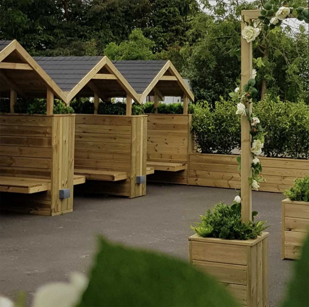 Bespoke booths, planters filled with greenery and archways wrapped with artificial foliage cream roses and ivy