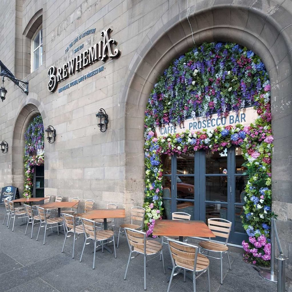 Brewhemia's exterior archways bursting with artificial roses, wisteria and assorted greenery for their pavement café