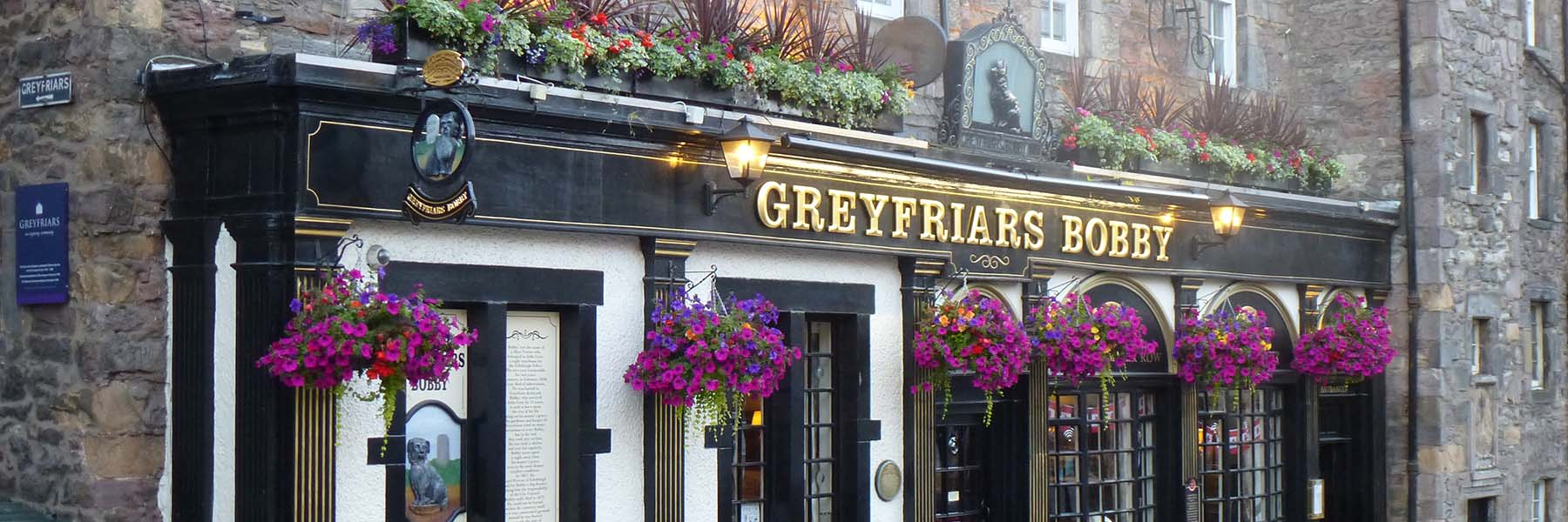 Bright blooming hanging baskets create a warm welcome at the famous Greyfriars Bobby pub in Edinburgh's old town