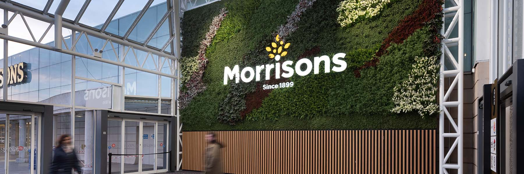 Huge 50 sq m green wall of artificial plants, Nordik Moss and Morrisons supermarket branding welcomes visitors at Gyle Shopping Centre Edinburgh